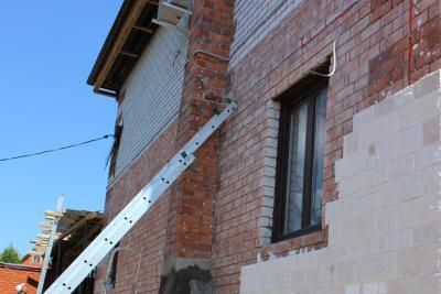Installation of manufactured stone veneer over sand-lime brick surfaces